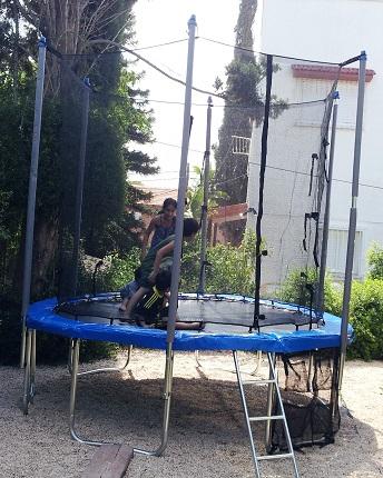 ילדים קופצים על טרמפולינה בחצר